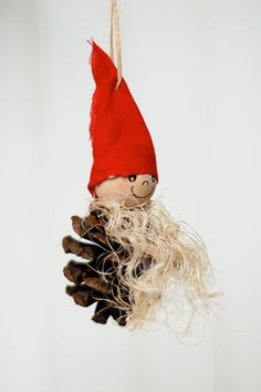 This is a Norwegian elf – complete with long beard and red cap, perched on a pinecone.