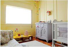 O móvel baixo amarelo, que era usado para acomodar a TV, agora serve de apoio e pode acompanhar o crescimento do bebê, ganhando novas funções