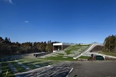 South Korean studio D·LIM architects completed The Forum, a green roofed multipurpose hall submerged beneath the ground on Jeju Island.