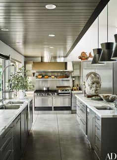 The kitchen boasts a Garland range and hood, Sub-Zero refrigerator, Bosch dishwasher, and Broan trash compactor   archdigest.com