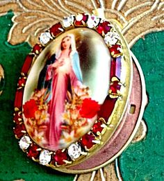 $89 Red Rhinestone Cameo Locket Virgin Mary Vintage Pendant (Image1) Porcelain cameo featuring the Blessed Mother Virgin Mary as the Immaculate heart standing amounst red roses. The oval cameo is surrounded by Deep ruby red baguette and round clear rhinestones. Inside the vintage locket is copper and brass - can hold 2 photo's and/or your prayer petition request to Mary.