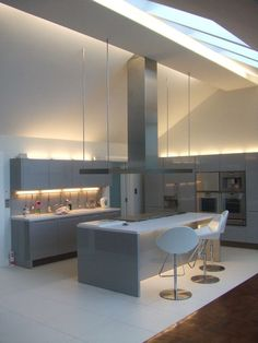 Astonishing Modern Kitchen Design Applicated With Gray Cabinetry And Metal Chimney Lighted By Hidden Lighting And Skylight
