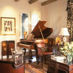Baby grand piano a bit crowded into corner, parallel to one wall; colors are warm; country style with wood beams, wood floors, area rug - Architect Ken Tate