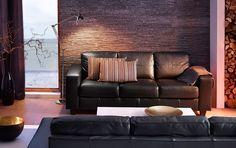 Kolmen istuttava musta SKOGABY-nahkasohva ja valkoinen LACK-sohvapöytä.