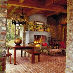 A backyard veranda in St. Francisville, Louisiana serves as a fireside retreat.  Built for warmth and beauty,  the fireplace is composed of a brick chimney, mantel, and firebox, and the exterior of the fireplace is covered with stucco as well. When designing this tranquil spot, architect Billie Brian raised the hearth for additional seating. Plus, by centering the fireplace between a brick opening and the exterior living room wall, she provided a nook for firewood.