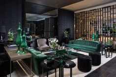 Avant Design, made up of sisters Cristina and Monica Souza, created a space around Tom Ford that  epitomizes the designer's aesthetic with a rich emerald and black color palette. Added velvet pieces provide an element of luxe that is synonymous to Ford.