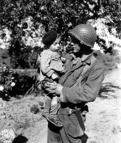 U.S. Army Pfc. Jesse De Vore of the 38th Infantry Regiment, 2nd Infantry Division, holds a young French boy following the Allied Landings at Normandy...