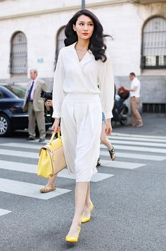 A wrap long sleeve dress is worn with yellow pointed toe flats and a two-toned handbag.