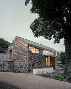 Eingangsbereich in umgebauter Scheune mit Mischung aus Glas Stahl und Naturstein