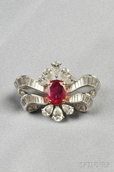 Platinum, Ruby, and Diamond Brooch, set with an oval-cut ruby measuring approx. 11.00 x 8.36 x 2.77 mm, and weighing approx. 2.10 cts., further set with pear-, baguette-, and full-cut diamonds, approx. total diamond wt. 5.00 cts., lg. 1 5/8 in.