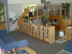 reggio Emilia inspired classroom. The entrance has pictures of all the children in the cubbies, and a large, cozy sofa. I want that loft.