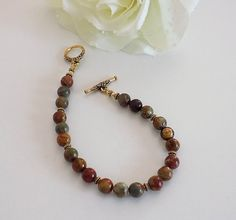 ❘❘❙❙❚❚ ON SALE ❚❚❙❙❘❘     The changing of colors on the leaves,and the cool crisp mornings. Fall is upon us. This gorgeous gemstone bracelet is perfect for your Fall wardrobe. The Red Creek Jasper Gemstone has colors of mustard yellow, olive green and burnt red perfect color combination.   Metaphysically, it is believed by some to bring balance and relaxation, and like all different Jasper, it is a stone of protection and grounding.   This wonderful gorgeous fits a size 8 inch wrist with a…