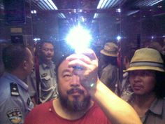 Religious-Icon-like self-portrait of Ai Weiwei    ::   Artist Ai Weiwei, surrounded by police, in a Chengdu hotel elevator in August 2009.  Ai took this photo with his camera phone, shortly after local police entered his hotel room and beat him.  He was in Chengdu, the capital of Sichuan, to support a local activist challenging the Chinese government's handling of the 2008 Sichuan earthquake.