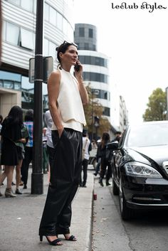 Womenswear Street Style by Ángel Robles. Fashion Photography from Paris Fashion Week. White and black outfit, black leather pants, white structured top and black sandals, Paris.