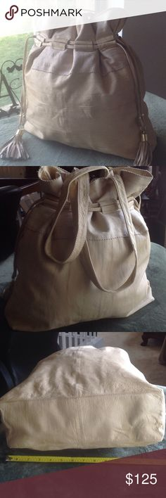 Top shop large cream leather drawstring purse/tote This is a very neat large tote or purse! Cream & taupe leather. Snap magnetic closure as well as a drawstring accent, trim has a zig zag cut, with tassels and gold tone hardware. Lightweight, so great for travel. *SEE pictures, inside lining has a yellow discoloration around bottom of bag & top of bag, so am thinking it has to do with what they treated the bag with? Also on inside top, a grayish? discoloration. A couple marks as shown on…