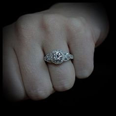 Gorgeous three stone diamond engagement ring setting with a beautiful Forever Brilliant moissanite center. Two lovely trillion shaped diamonds sit adjacent to a beautiful round moissanite center stone