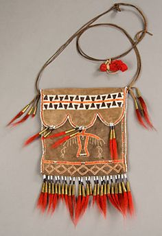 Wôbanaki Men's Clothing from 1700 This deerskin pouch is decorated with tufts of deer hair dyed red, embroidery of flattened, dyed porcupine quills, white glass beads, and cones made from a copper kettle. The cones would serve as bells, making a pleasant noise when the bag moved. A bundle of tobacco is attached to the bag's strap.Porcupine quill embroidery, beading, fringe, and ribbons might be added to the edges of clothing, both to offer protection and to encourage connections with…