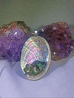 Most people see Abalone in its polished stage, not this pendant! Don't let the polished product fool you, those vibrant colors are still just as neon and beautiful! Not to mention the bismuth complimenting, with the natural rainbow colors bismuth casts. Hung by a silver 16inch