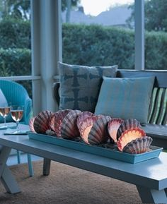 Light clean shells using candles or LED lights-- Stunner of a coffee-table scape. Imagine this at a beach wedding?