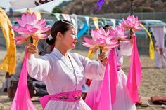 Korean women in traditional clothing performing a buddhist ceremony.
