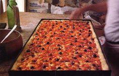È una specie di focaccia condita con un sugo di pomodoro, aglio, capperi (meglio se conservati sotto sale), olive taggiasche, origano e sarde fresche che danno