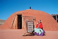 Navajo woman weaving outside her hogan