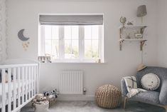 Stylish pale grey, wood and white unisex nursery, including Boori cotbed, John Lewis armchair, Ikea picture ledges and Tesco lighting.