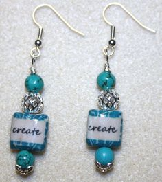 "Handcrafted by Teal Palmetto, LLC. If you know of an artist, writer, or any other type of creative person (even if you are one yourself), these earrings are picture-perfect for you!!  Decoupaged ""create"" beads in teal, black, and cream join with silver metal and teal ceramic beads in this pretty look.  This pair his silver fish hook ear wires.  Price: $12."