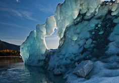 A melting segment of juneau, alaska, USA's mendenhall glacier moves a smaller boulder from the mountains to the surface of mendenhall lake.