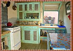 The Red Cat House in Taos with a distressed turquoise pie safe hutch and loaded with colorful antiques.