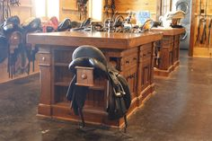 A clever multi-purpose center island in a tackroom with pull out saddle racks