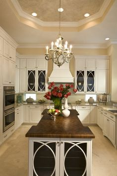love the glass in the cabinet doors. also, this look could likely be accomplished with off the shelf cabinetry. a slight bump out at the sink and a few glass fronts really make it.