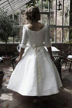 Obsessed!!! I would love to find a dress like this. How feminine and sweet. Sleek tea length dress, white with cream ribbon bow, boat neck and cuffed half sleeves, row of buttons down the back