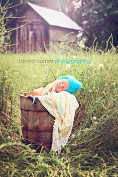 Newborn baby in ice cream bucket with homemade turquoise knit hat.tamra horner photography
