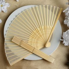 Asian Silk Folding Fans - Ivory | eFavorMart / Add a classical Asian touch to your wedding, or a special event by presenting your esteemed guests with this special souvenir. Our stylish silk wedding hand fan is intricately handcrafted with a bamboo structure. The framing and spines are crafted from hand-picked bamboo and durably glued with a seamless cut piece of silk to fashion this immaculate magnum opus. Give these swish fans to your respected guests and let them create the lasting memory…