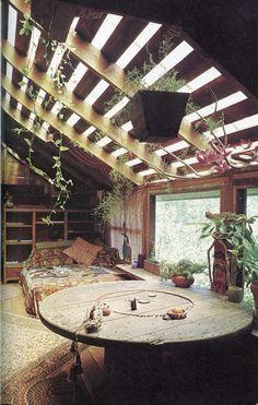 天井から観葉植物が垂れさがった、まるでプライベートな植物園のようなリビングです。天然木のどっしりした大きな丸テーブルが存在感を放っています。