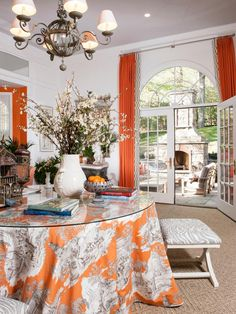 DC Design House: Originally built as a ballroom, Kelley Proxmire of Kelley Interior Design is inspired by the room's Palladian windows that reminded of her Versailles to design a L'Orangerie. By using Manuel Canovas toile, various textures and materials including a faux stone table base with honed marble top, whitewashed demilunes and an antique chair painted a glossy orange, Proxmire blends the room's theme with an orange and gray color scheme.