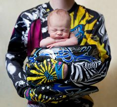 In this one babies bum is wrapped so the baby is sat crossed legged. You snuggle baby with the helmet in between your knees on the floor then gently lower babys bum into the helmet. You need to get dad to push his elbows towards camera a bit as the perspective will distort them otherwise, and shoulders down.