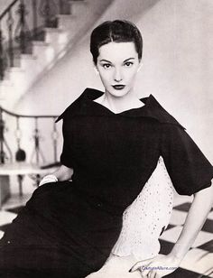 """...amount of work that goes into the details.  Case in point, this little black dress by David Marcus from 1951.  A lot of effort went into getting that collar just right so it frames the face and neck in such a beguiling manner.  The sleeve is not just a straight thing that hangs there.  It is cut with a slight bell shape and gathered into a cuff at the elbow.  The details are interesting enough that just a simple pair of earrings are all you need."""