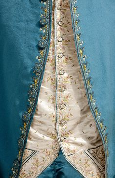 Detail front view, 3-piece suit, 18th century. Blue silk, embroidered with floral motifs on front border; waistcoat: cream silk satin, embroidered with floral sprays and floral motifs.