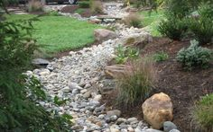 10 Stunning Landscape Ideas for a Sloped Yard - pebbles in the 'valley'