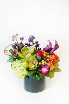 Deep burgundy calla lilies, green cymbidium orchids and orange roses are a colorful and complementary mix of flowers in this modern design. Peach hypericum berries and green hydrangea provide a neutral backdrop to set off the rich purple and orange tones. From Nosegay Flower Shop via @BloompopHQ