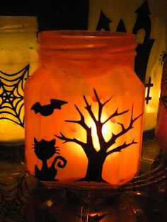 Halloween decoration - glue & orange food coloring. Mod podge black fabric silhouettes to the mason jar