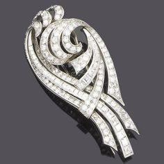 A diamond brooch, circa 1950  Of pierced scrolling design, set with rows of brilliant and square-cut diamonds, diamonds approx. 4.95ct. total, length 6.8cm.