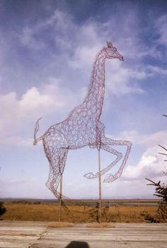 Escultura de alambre con la figura de una jirafa en color rojo