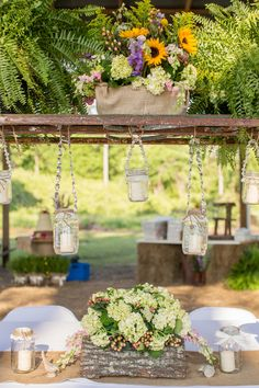 Log, ladder, mason jars and wild flowers combine in this stunning tablescape.