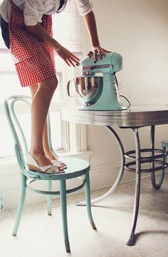 I want this kitchen aid!! Lovely apron & table as well.... really unsure why she is standing on the chair.