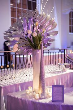 Fresh white tulips and oversized monstera leaves spray painted silver hover over silver decor and mercury votives.