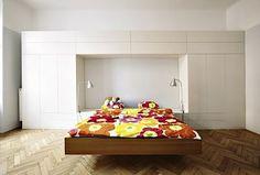 Geometrická hra bílých obdélníků dvířek a velké niky je funkčním a zároveň výtvarným pojetím šatní stěny. Umístěná v záhlaví postele uvolňuje prostor před protější stěnou.