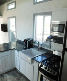 The kitchen is equipped with a white farmhouse sink and gooseneck faucet, four burner gas range with vented range hood, white shaker style cabinets, and a Corian countertop with flint backsplash.